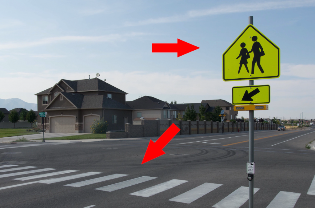 If you see two people on the pedestrian sign and ladder bars on the roadway, you're at a school crosswalk, which means you have to stop for anyone in the crosswalk, regardless of which half of the roadway they're on.